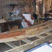 The bottom plank with the centerboard trunk stiffeners in place being screwed to the building platform by David Ramírez