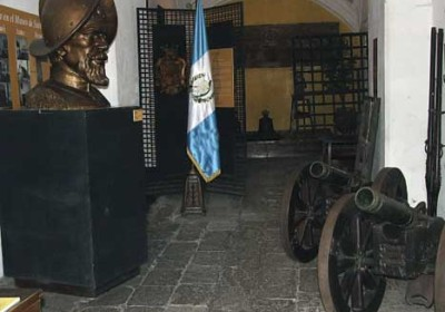 Entry hall of the Museo de Santiago, a large bust of Pedro de Alvarado looks down on two 18th century howitzers; behind are six-gauge wall guns.