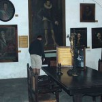 A visitor is admiring the original sword of Pedro de Alvarado, which is in the case below his portrait. Surrounding it are other Guatemalan dignitaries.