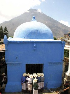 Admirers look in on Maximón from the side window of his chapel in the churchyard, which he occupies for only a few days per year. Volcán San Pedro towers in the distance across the bay of Santiago.  (photo: Victoria Stone)
