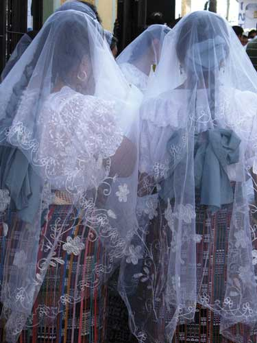 Hundreds of women line the streets and participate in their colorful shawls; young women, little girls, and grandmothers wear the white lacy veils that mark their devotion. (photo: Victoria Stone)