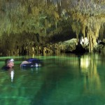 Janson uses an inner tube to keep his equipment dry as he explores a water-filled cavern