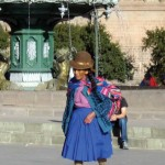Woman wears colorful Peruvian crafts in Cuzco