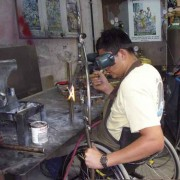 Efrain welds a custom wheelchair frame—the workshop will produce 200 wheelchairs this year
