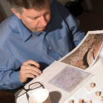 Dr. Stephen Houston examines photographs and artifacts from the Royal Tomb.