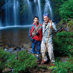 Guide Josue (left) and author Janson stop for a photo op beside some beautiful waterfalls