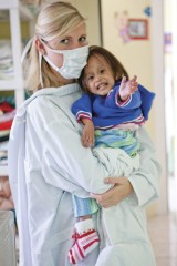 Volunteer Melanie H. with a child recovering from malnutrition. (photo: Ray Conway)