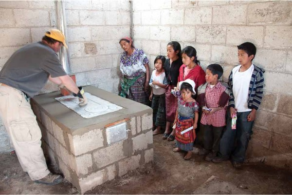 A Guatemalan family watches the finishing touches put on their new efficient stove with chimney pipe
